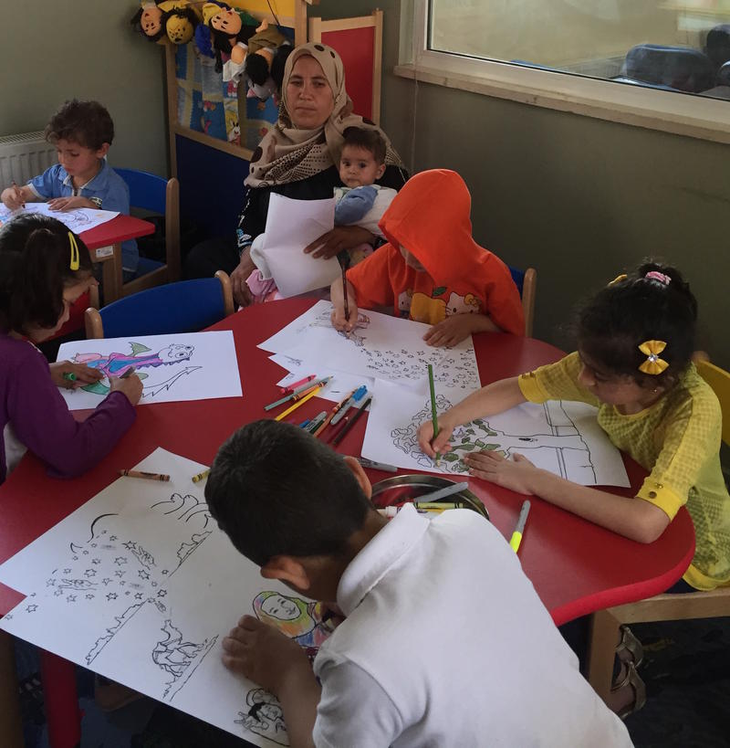 Refugee mother and child and refugee children coloring in Jordan