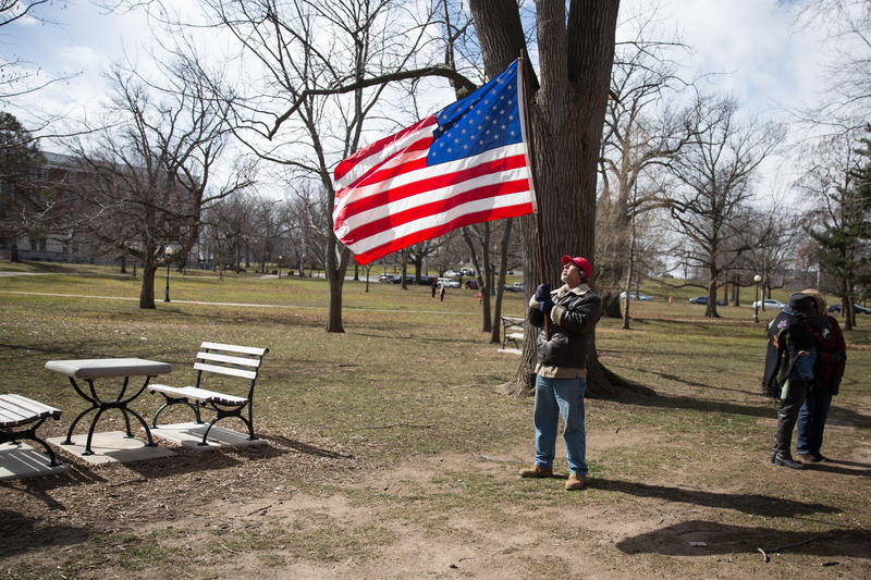 "Kevin Anderson of Portland, Connecticut stands with an American Flag in Hartford's Bushnell Park. He says President Trump's message resounds with him because he's ""anti-establishment."""
