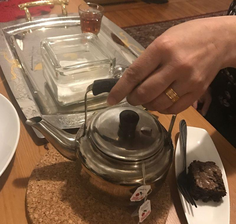 Mona's tea service was one of the only non-essential items she was able to pack when she left Jordan last month. She serves tea and brownies to guests in her new apartment.