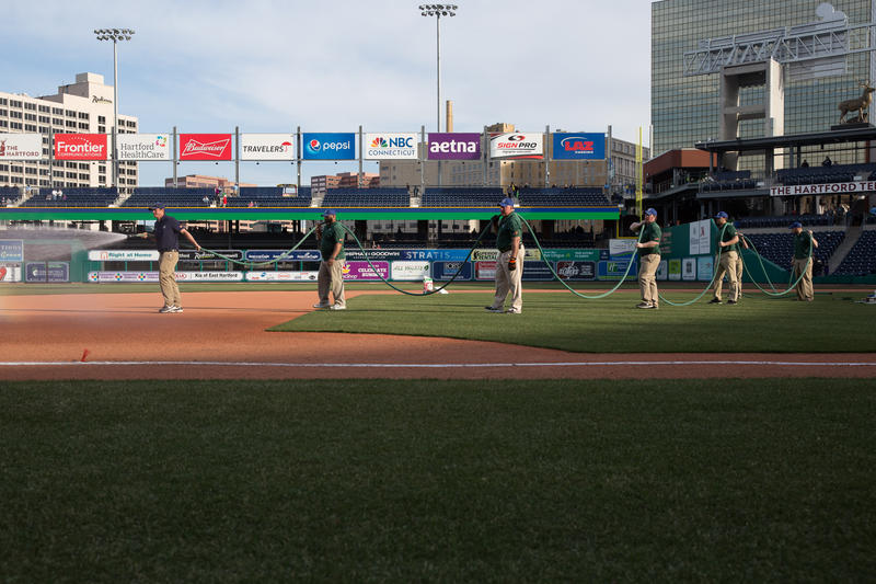 The turf crew, led by Kyle Calhoon, watering the infield on opening day.