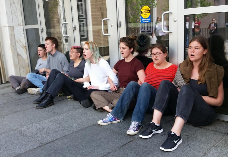 People sit in front of a federal immigration building in Hartford to protest the deportation of a Derby man.