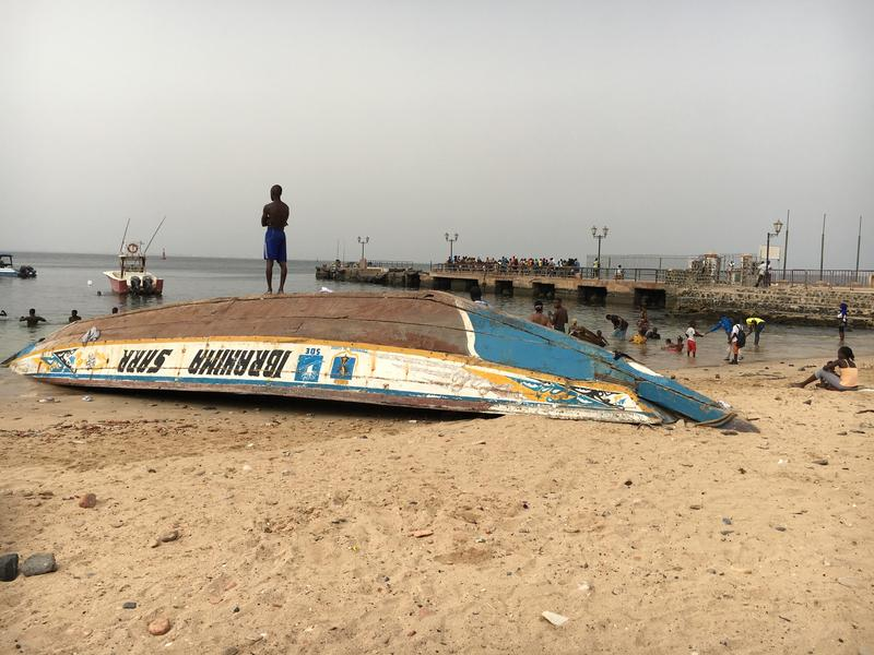Beach on Goree Island off the coast of Dakar. A man stands on a boat used by fisherman in the area.