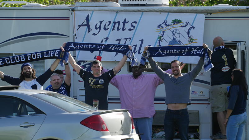 The Agents of Hale, Hartford City FC's support group, pose outside of an RV owned by a club member.