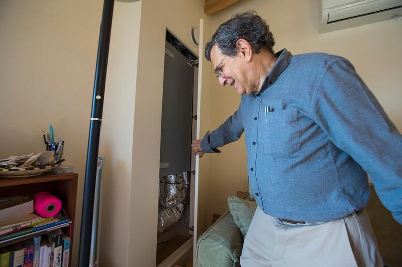 Fred Gordon opens a panel in the wall of his apartment to show the heat recovery ventilator. It provides fresh air, transferring 95 percent of the heat collected from the apartment and recirculating it with cold air from outside.