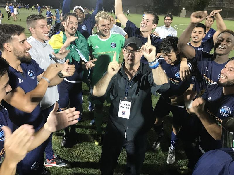Zack Henry (pictured in the middle) celebrates Saturday's NPSL title win with Elm City players.