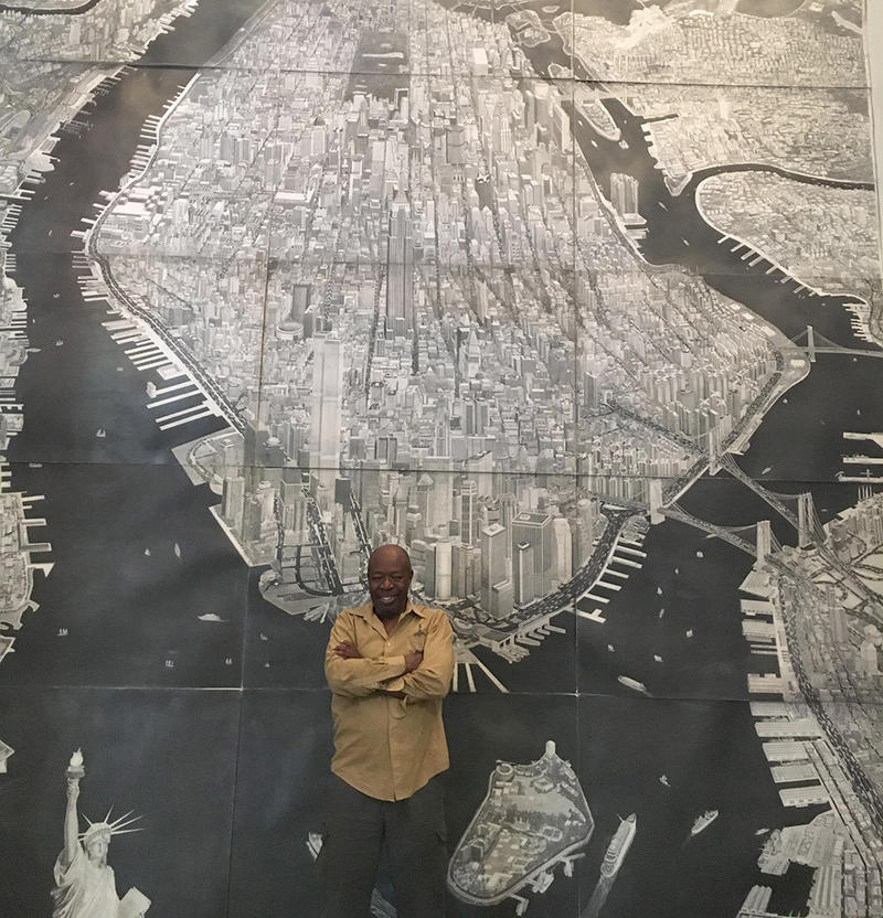 """Krikko stands in front of an original drawing of """"The Super Big Apple"""" in New Haven's Hill Museum of Arts."""
