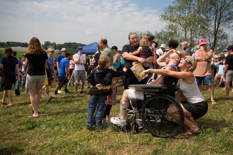 Rebecca Theriault (immediately behind wheelchair) looks up at the eclipse with her mom on UConn's Horsebarn Hill.