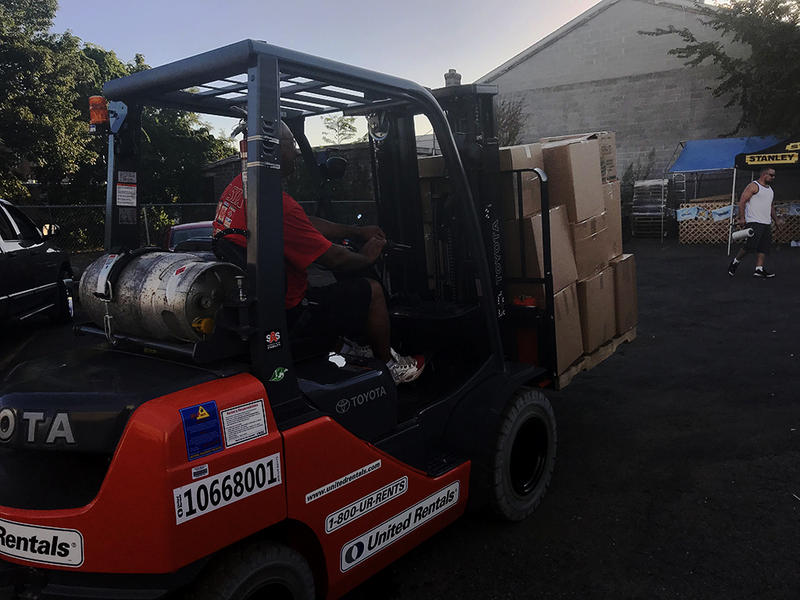 Hector Torres runs a forklift to move and organize pallets filled with donations in New Britain.
