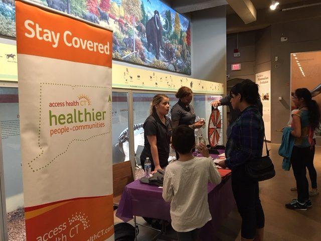 Grace Montesi, an outreach team worker for Access Health CT, discusses open enrollment at festival, sponsored by Junta For Progressive Action, at the Peabody Museum, New Haven.
