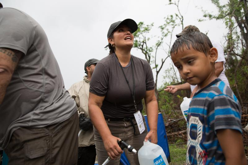 Veronica Montalvo fills up a water jug for a boy in Salinas, Puerto Rico.