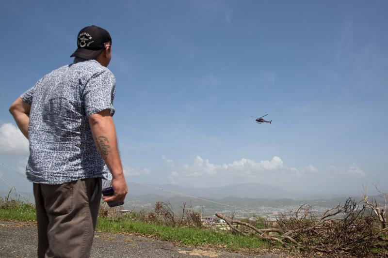 Angel Rodriguez watches a helicopter that appears to be surveying electrical lines on the top of a mountain peak in Humacao.