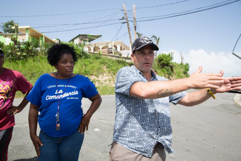 Angel Rodriguez speaks to Maria Castro, a community leader. He tells her he'll connect her with a nonprofit looking to donate water filters to the relief effort.