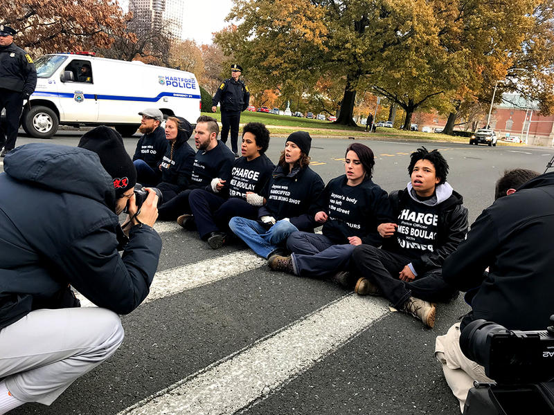 """Protesters wearing """"Charge Police Officer James Boulay With Murder"""" shirts lock arms and sing on Capitol Avenue."""