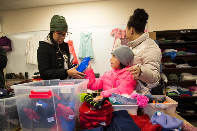 In the hurricane relief center in Hartford, Kaliel Diaz (center) goes through winter clothing with her mom Nydia Marcano (left) and her cousin Marlene Hernandez (right).