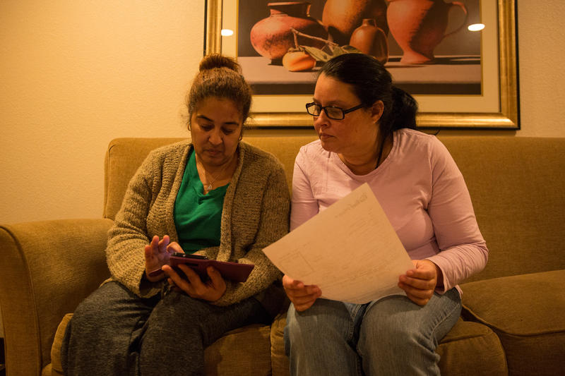 Carmen Cotto and Wanda Ortiz read through emails sent to them Thursday afternoon when city officials were trying to work out logistics for the families to stay at the hotel after FEMA funding ended that day.