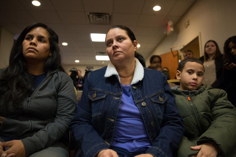 Hurricane evacuees Yara Vasquez (left) and Wanda Ortiz (center) watch a press conference at the hotel they were living in with their families under a FEMA program on January 19, 2018.