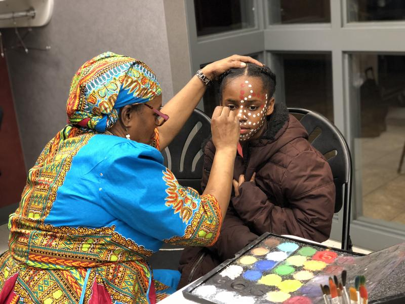 "Before a screening of ""Black Panther,"" artist Martha Walker-Dawkins paints the face of Zaniah Welsh, a fourth-grader at West Hartford's Smith STEM School. Engineer David Johnson sponsored the event to inspire students."