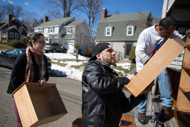 Hurricane evacuees Israel Rivera (center) and Pedro Bermudez (right) load a moving truck with furniture that residents of Avon and West Hartford donated for families who relocated to Connecticut from Puerto Rico.