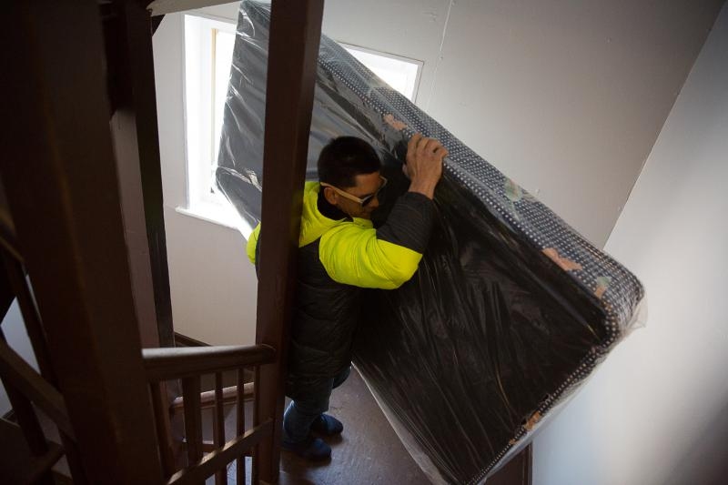Rafael Febres moves a mattress into his apartment in Hartford where he recently moved with his wife and son.