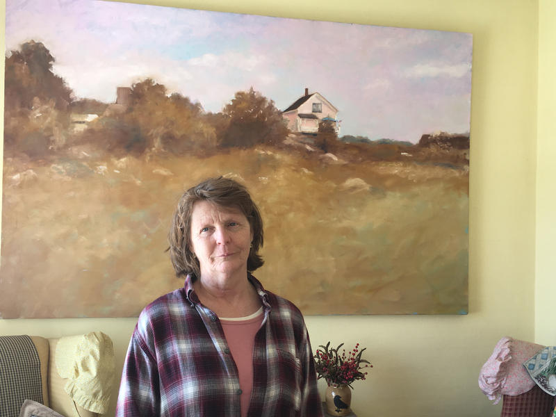 Susette Kelo stands in front of a picture of her little pink house, hanging in her present home in Griswold
