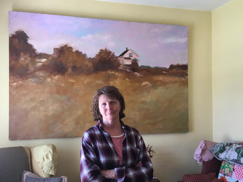 "Susette Kelo standing in front of a painting of her Fort Trumbull ""little pink house"""