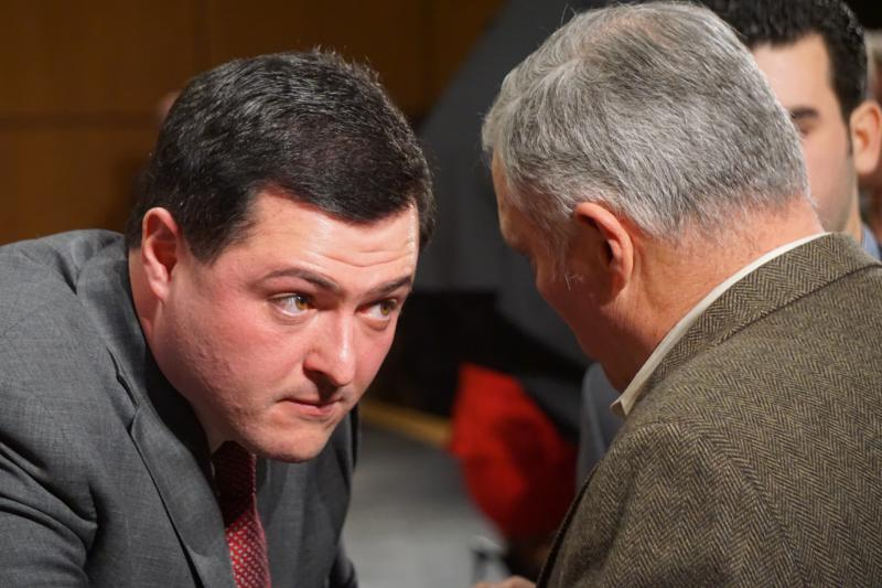 Timothy Herbst consulting with his father at a GOP forum in January.