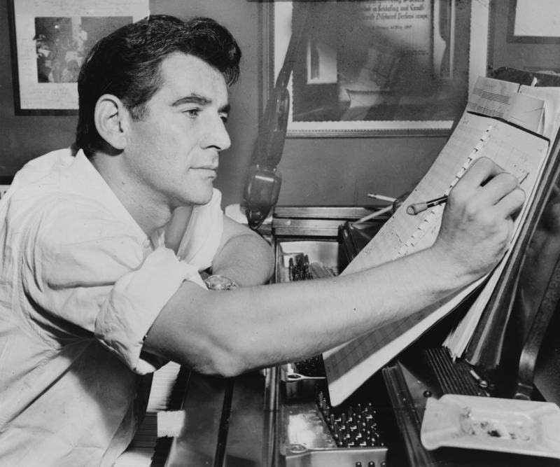 Leonard Bernstein seated at piano, making annotations to a musical score.