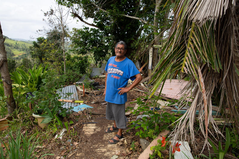 Angel Luis Cotto stands in the debris of his backyard clubhouse, destroyed by Hurricane Maria.