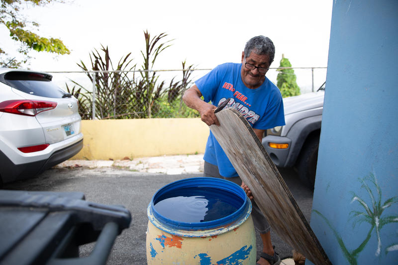 Angel Luis Cotto puts a wooden board over one of the two barrels of water his family prepared for a potential hurricane.