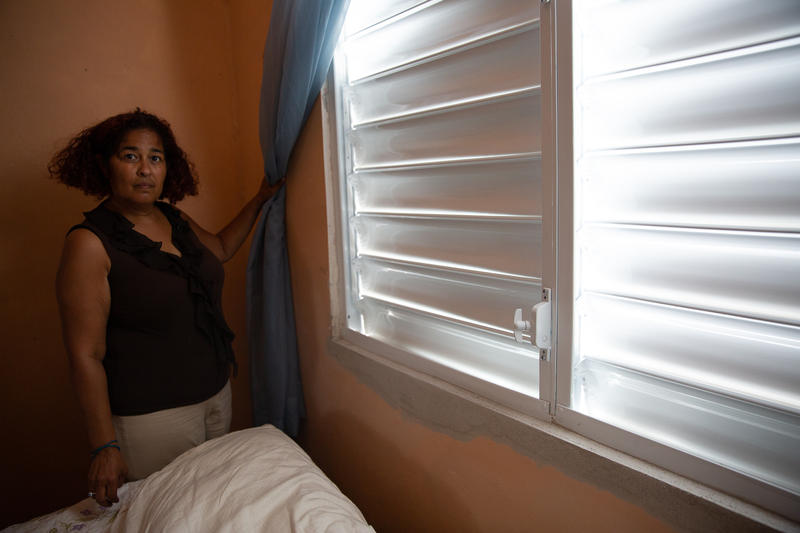 Carmen Cotto in a bedroom of her parent's house next to newly installed windows. She says that while people are preparing for the next storm, they still haven't really dealt with the first.