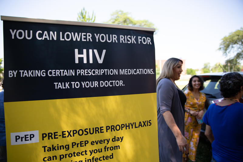Tatiana Melendez, standing tall next to the PrEP promotional poster, is doing HIV prevention outreach at Hartford's Barnard Park on a recent Friday. Melendez, a.k.a. Lady Tatiana, began working for the Community Renewal Team in May as its PrEP navigator.