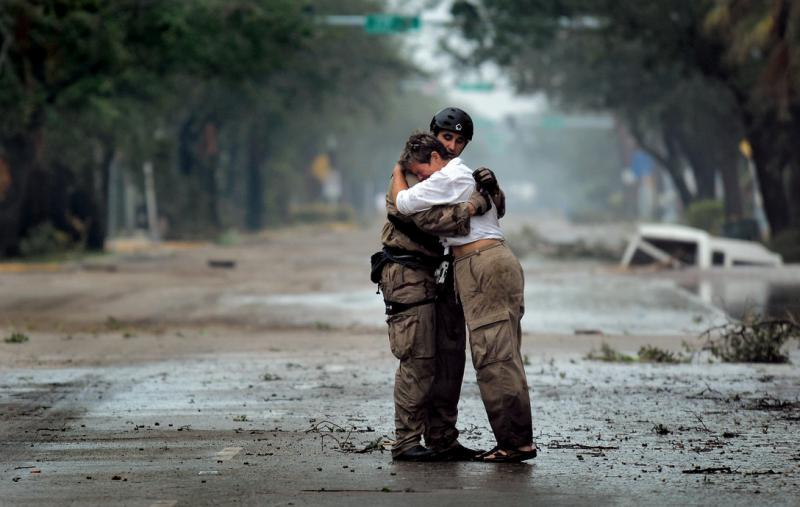 A first responder consoles a hurricane victim in Texas