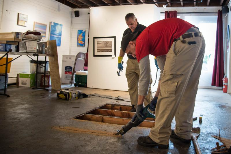 Paul Byzowyckj of the Atlantic Restoration & Remodeling Group cuts a section of water-rotted floor of the Art League of New Britain building as his coworker Gordan Hutchinson looks on on Oct. 3, 2018.