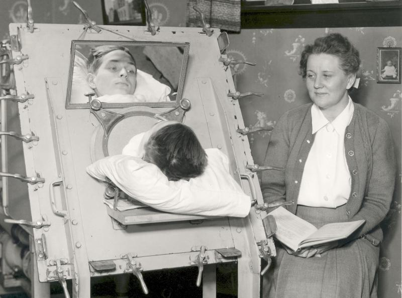 A high school boy studies with a volunteer teacher at his home, in an iron lung provided by the New Haven Hospital (c. 1943)