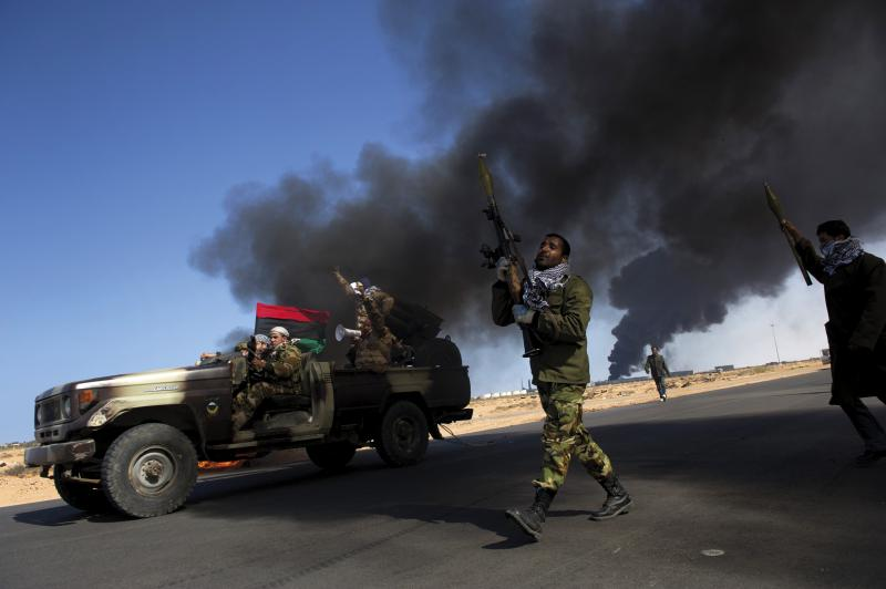 Opposition troops burn tires to use the thick smoke as cover from air strikes at the main  checkpoint near the refinery as rebel troops pull back from Ras Lanuf in eastern Libya, March 2011.