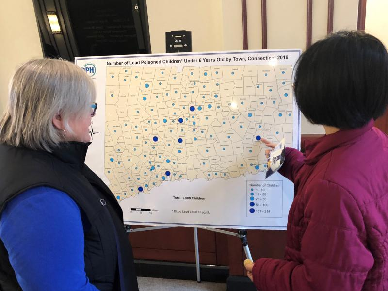 Tracy Min Hung, right, a state public health epidemiologist, shows Molly Magoon a map she made showing incidences of childhood lead poisoning across Connecticut. Magoon works for the U.S. Environmental Protection Agency.
