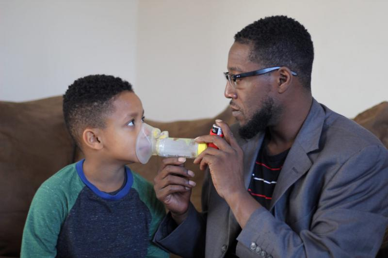 Robert Carmon, and dad, Chaz demonstrate the inhaler used twice daily to control Robert's asthma.