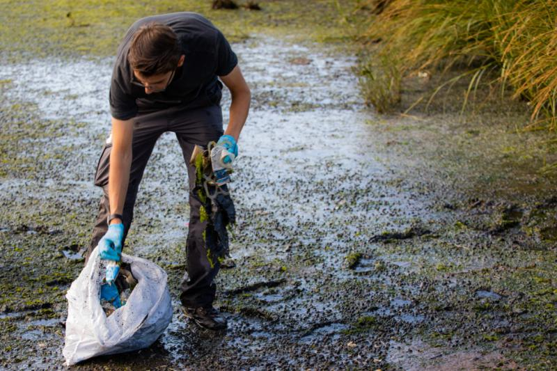 Stephen Urchick, 24, stuffs a handful of plastic bottles and six-pack rings into a garbage bag. Urchick volunteered to help clean Long Wharf as part of the Save the Sound program run by the Connecticut Fund for the Environment.