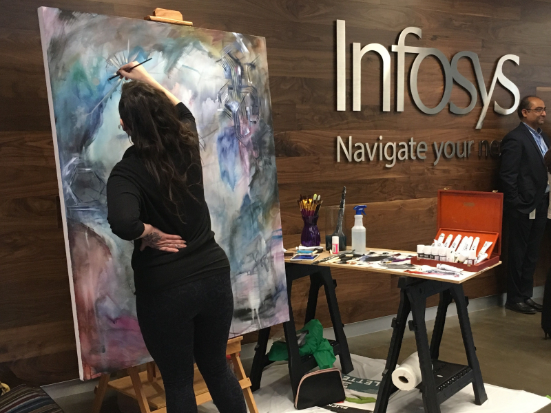 Artist Bri Dill from South Windsor creates a painting at the grand opening of Infosys' Hartford innovation hub.