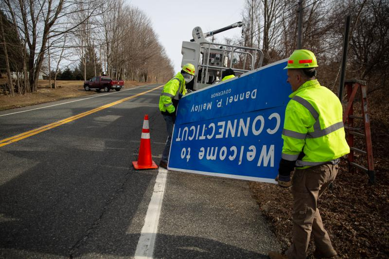 State workers remove a highway welcome sign in Salisbury on Monday, replacing it with a new sign with Governor Ned Lamont's name.