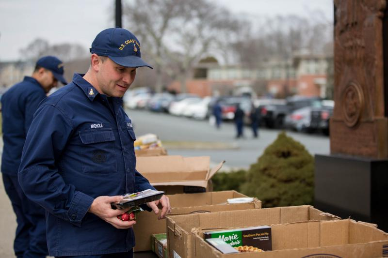 Outside of a hall on campus at the Academy, senior chief Brian Nichols grabs some food after volunteering to get his fellow service members fed.
