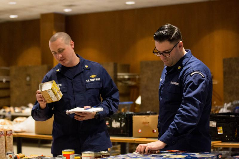 Petty officers Nick Saporito (left) and Joe D'Aleo (right) browse through donated items inside the United States Coast Guard Academy's Leamy Hall on January 16. Active-duty members of the Coast Guard aren't being paid during the shutdown.