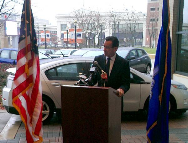 Governor Dannel Malloy addresses reporters outside the 2013 Connecticut International Auto Show in Hartford. He announced a new round of incentives for building additional electric vehicle charging stations around the state.