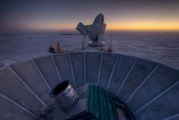 The sun sets behind BICEP2 (in the foreground) and the South Pole Telescope (in the background). This month, BICEP2 discovered the first direct evidence of cosmic inflation.