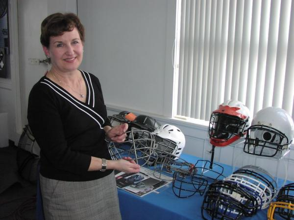 Mary Fitzgerald of Acme Wire Products, based in Mystic, with lacrosse helmets. Acme Wire manufactures the face guards.
