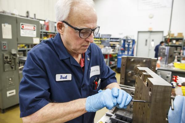 Bud Emrie, Senior Moldmaker at NPI Medical, performs maintenance on a production multi-cavity mold in the tool room.