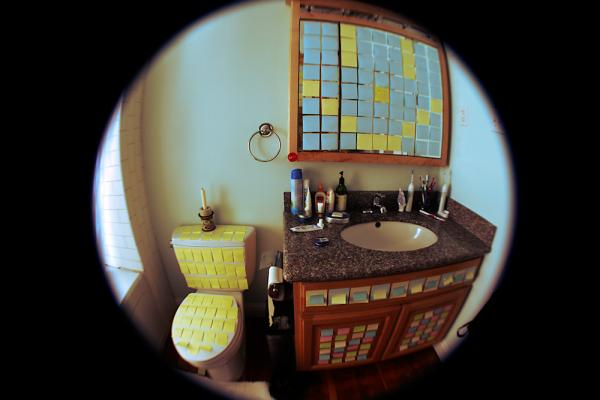An April Fools' Day prank in a bathroom includes Post-It notes on everything.
