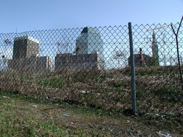 Downtown Springfield as seen from a fence along the riverfront. A highway and a rail line separate the river and downtown.