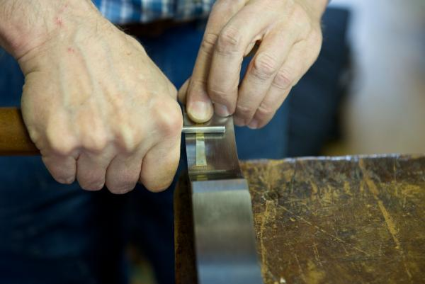 In a reed curving block, Daniel Kingman adds a curve to a brass reed tongue.