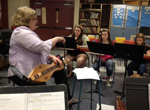 Teacher Laurel Schwartz guides students at the Middle School of Plainville in playing dulcimers.